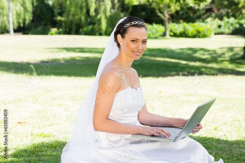 Smiling bride using laptop in garden