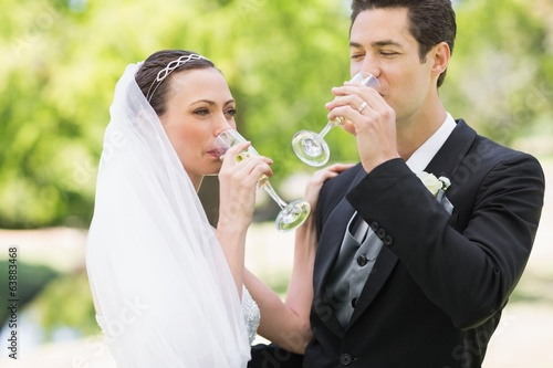 Newlywed couple drinking champagne