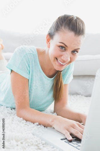 Cheerful woman lying on rug using her laptop