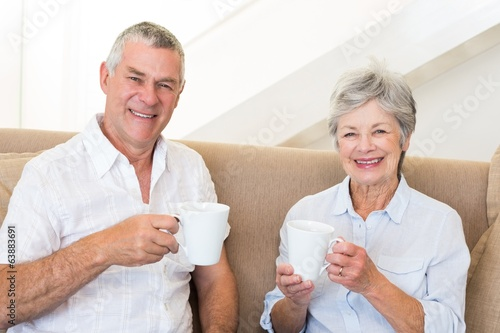 Senior couple sitting on couch drinking coffee smiling at camera