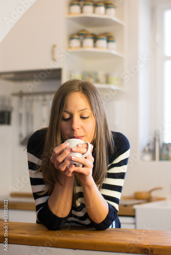 woman enjoys fresh coffee in the morning with sunrise at home