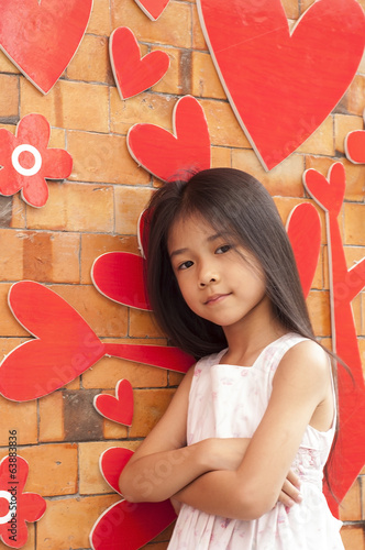 Little Asian girl with red heart on brick wall.