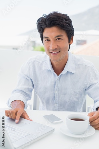 Smiling man having coffee and using laptop