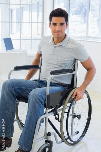 Casual businessman in wheelchair smiling at camera