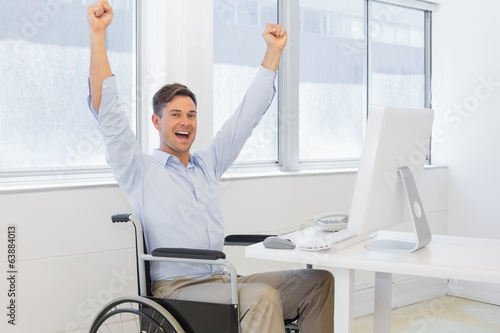 Casual businessman in wheelchair cheering at his desk
