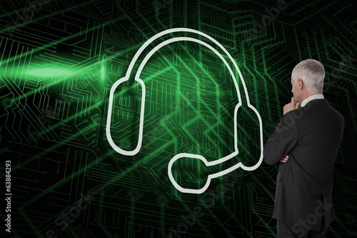 Composite image of headset with businessman looking