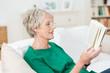 Leinwanddruck Bild seniorin liest ein buch