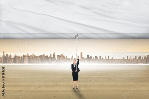 Composite image of businesswoman pulling a white screen