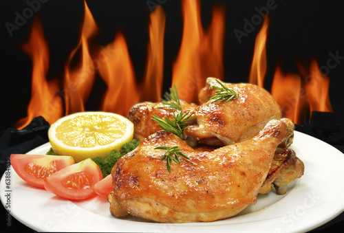 Grilled chicken thigh with vegetables on white plate.