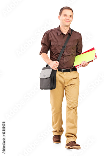 Young man walking with books