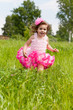 cheerful girl in a pink dress runs on a grass