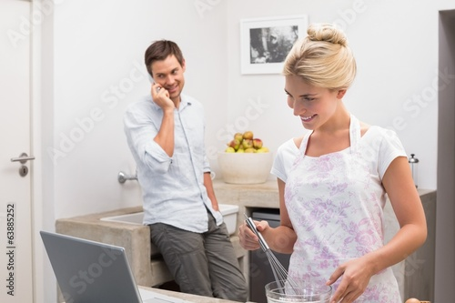 Smiling woman preparing cookies while man on call in kitchen