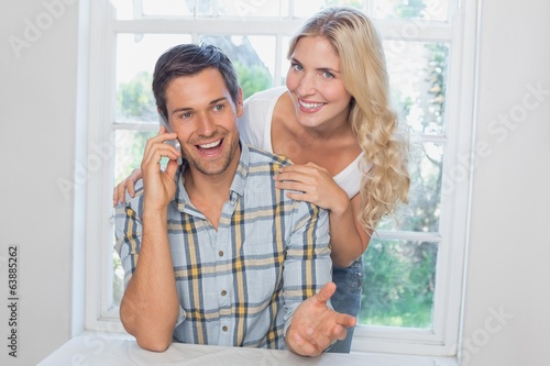 Happy man on call besides a beautiful woman