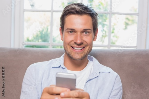 Portrait of a casual man reading text message on sofa