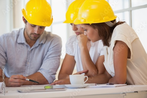 Architects in yellow helmets working on blueprints