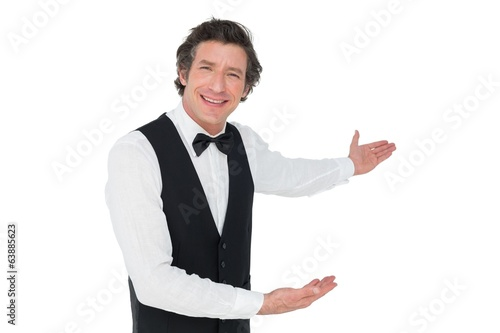 Happy waiter welcoming over white background