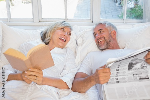Cheerful mature couple with newspaper and book in bed