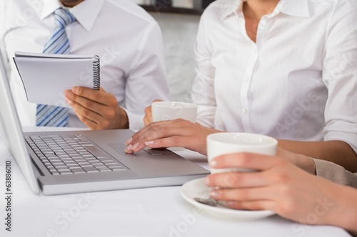 Mid section of three business people using laptop