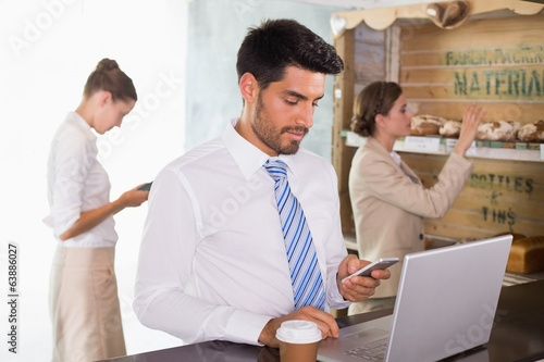 Businessman using mobile phone and laptop in office cafeteria