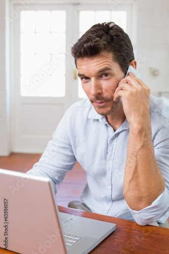 Smiling man using laptop and mobile phone