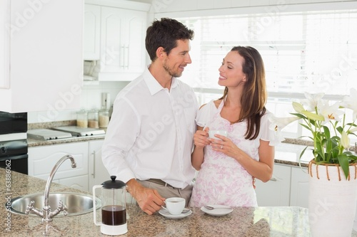 Happy young couple having coffee in kitchen