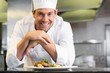 Smiling male chef with cooked food in kitchen