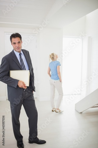 Well dressed real estate agent with blurred woman in background