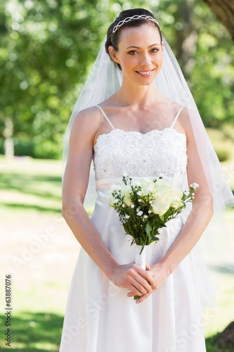 Bride holding bouquet in park
