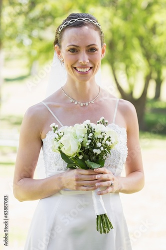 Woman in wedding gown holding bouquet in garden