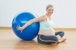 Happy pregnant woman sitting beside exercise ball