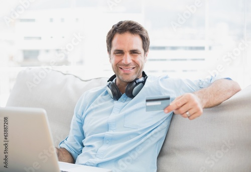Happy handsome man sitting on sofa online shopping with laptop