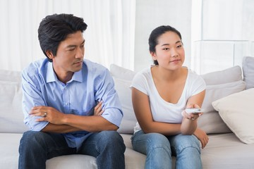 Man looking at girlfriend changing channel