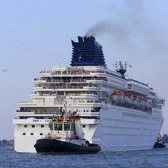 Powerful tugboat while accurately manoeuvre the cruise ship