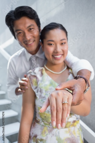 Couple showing engagement ring on womans finger