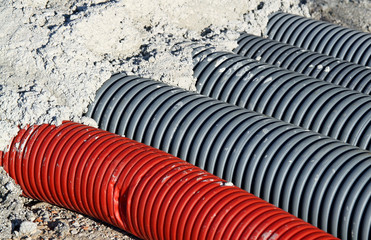 pvc corrugated hose and four gray pipes for laying electric cabl