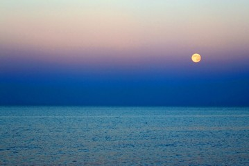Moon that rises above the blue sea at nightfall