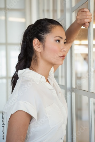 Casual businesswoman looking through window