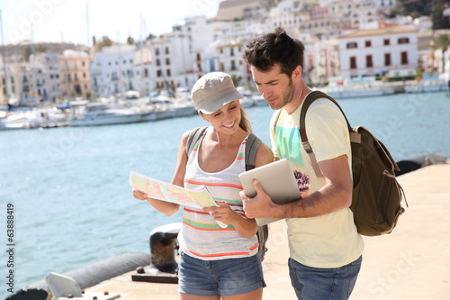 Couple of tourists looking at city map of Ibiza