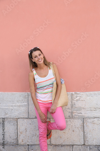 Trendy girl standing against colorful wall