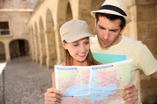 Couple of tourists looking at map