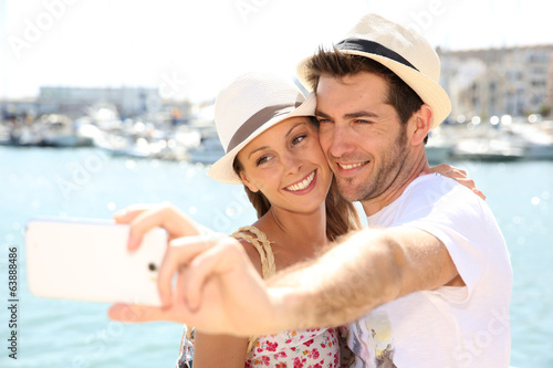happy couple of tourists taking pictures with smartphone