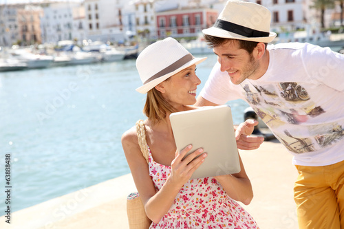 Couple of tourists websurfing with tablet