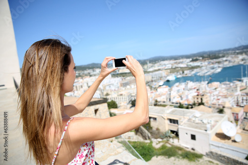Young woman taking picture of Ibiza town scenery