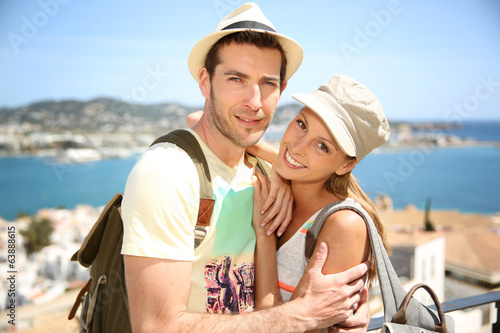 Cheerful couple of tourists with hat and backpack