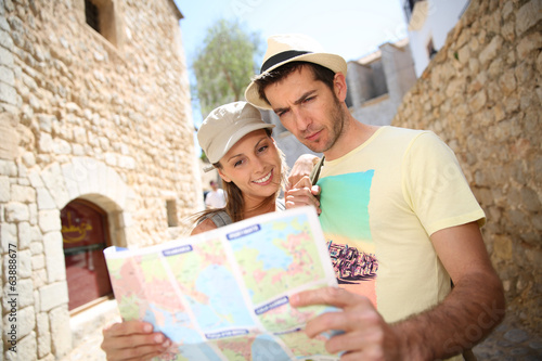 Couple of tourists in the street reading city map