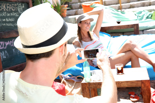 Man taking picture of girlfriend with smartphone