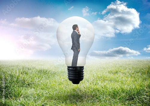 Composite image of thinking businessman in light bulb