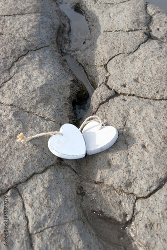 two wooden love hearts on the sand bank