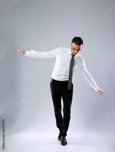 Businessman walking on invisible rope on gray background