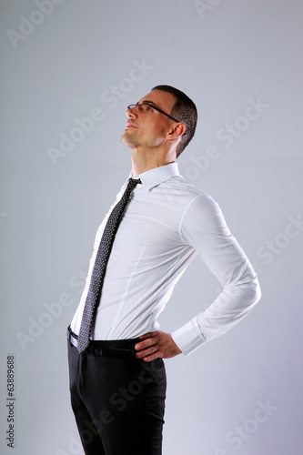 Portrait of a businessman stretching on gray background